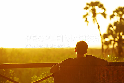 Buy stock photo Rearview shot of an unrecognizable man having a drink outside at a resort in nature
