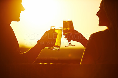 Buy stock photo Silhouette shot of a young married couple having a drink outside at a resort in nature