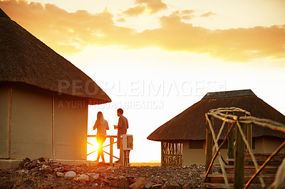 Buy stock photo Rearview shot of an unrecognizable couple having a drink while standing on their suites veranda at a resort in nature