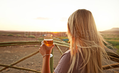 Buy stock photo Rearview shot of an unrecognizable woman drinking beer at a resort in nature