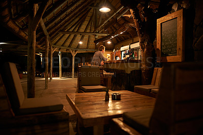 Buy stock photo Shot of a young man having a drink by the bar at a resort in nature