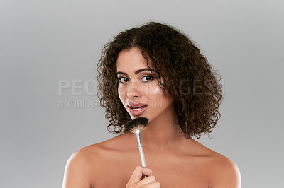 Buy stock photo Studio shot of a beautiful young woman using a make up brush against a gray background