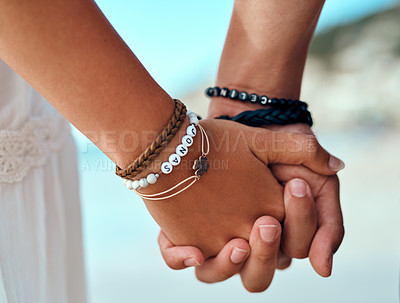 Buy stock photo Cropped shot of a couple holding hands at the beach