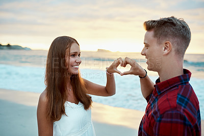 Buy stock photo Shot of a happy young couple making a heart shaped gesture with their hands at the beach