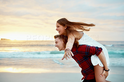 Buy stock photo Shot of a happy young enjoying a piggyback ride at the beach