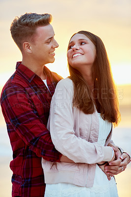 Buy stock photo Shot of a happy young couple spending a romantic day at the beach