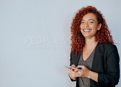 Buy stock photo Portrait of a young businesswoman using a cellphone against a grey background