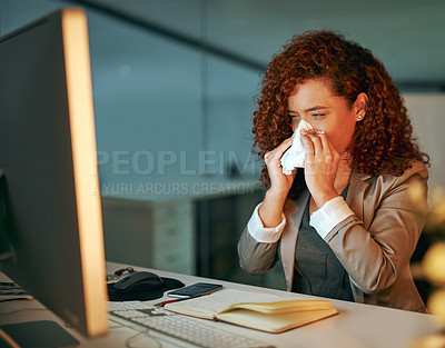 Buy stock photo Shot of a young businesswoman blowing her nose while working late in an office