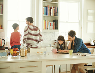 Buy stock photo Shot of a mother and daughter reading a newspaper while a father and son wash dishes at home