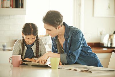 Buy stock photo Shot of a mother and her little daughter reading a newspaper at home