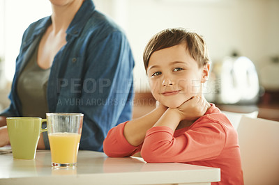 Buy stock photo Portrait of an adorable little boy enjoying breakfast with his mother at home