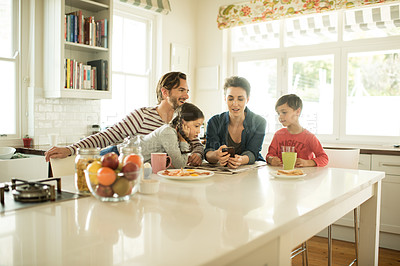 Buy stock photo Shot of a family using a cellphone together at home