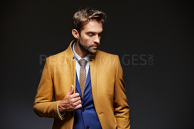 Buy stock photo Studio shot of a handsome young businessman posing against a dark background