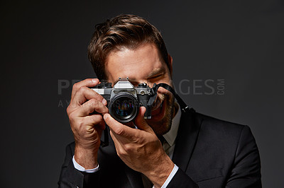 Buy stock photo Studio portrait of a handsome young man taking pictures against a grey background