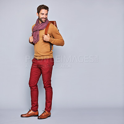 Buy stock photo Studio shot of a handsome young man carrying a backpack against a grey background
