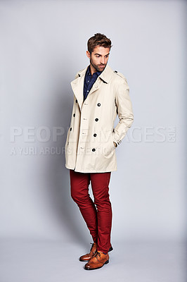 Buy stock photo Studio shot of a handsome young man posing in a trench coat against a grey background