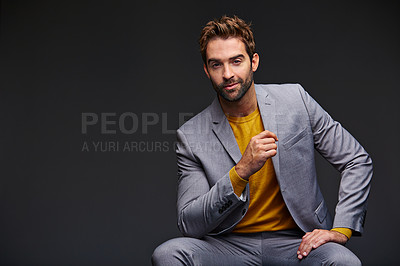 Buy stock photo Studio portrait of a handsome young businessman sitting against a grey background