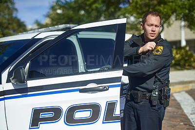 Buy stock photo Cropped shot of a handsome young policeman radioing in with headquarters