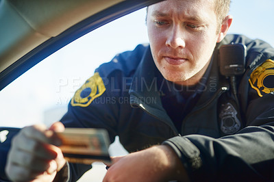 Buy stock photo Cropped shot of a handsome young male traffic officer checking a license at a roadblock