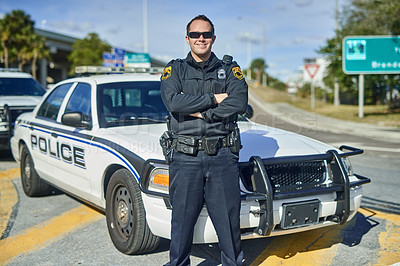 Buy stock photo Cropped portrait of a handsome young policeman standing with his arms crossed while out on patrol