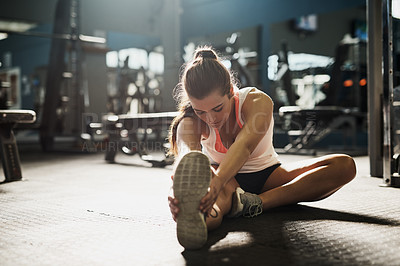 Buy stock photo Shot of a young woman doing stretch exercises at the gym
