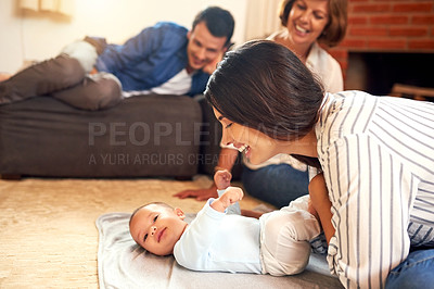 Buy stock photo Cropped shot of an attractive young woman and her baby boy bonding at home with the family in the background