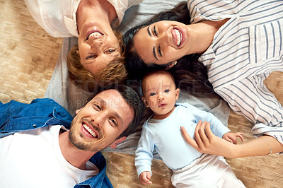 Buy stock photo High angle portrait of an affectionate family of five lying down on the living room floor
