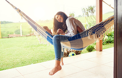 Buy stock photo Full length shot of an attractive young woman and her son bonding outside on the hammock