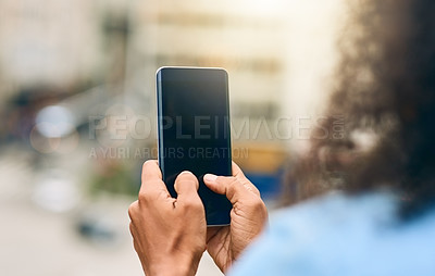 Buy stock photo Cropped shot of an unrecognizable woman using her cellphone while in the city