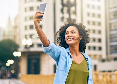 Buy stock photo Shot of a young woman taking a selfie on her cellphone while out in the city