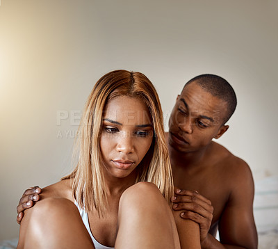 Buy stock photo Shot of a young woman looking upset while her boyfriend tries to comfort her