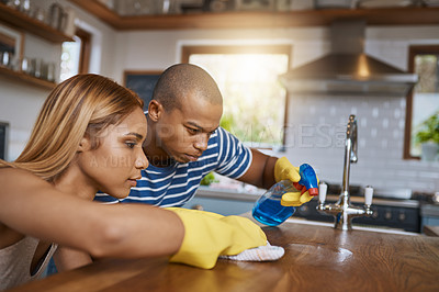 Buy stock photo Shot of a young couple cleaning up the kitchen at home