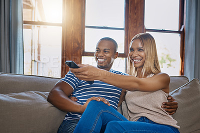 Buy stock photo Shot of a happy young couple relaxing and watching tv together on the sofa at home