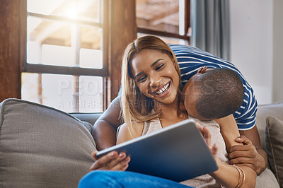 Buy stock photo Shot of a happy young woman using a digital tablet on the sofa while her husband kisses her from behind