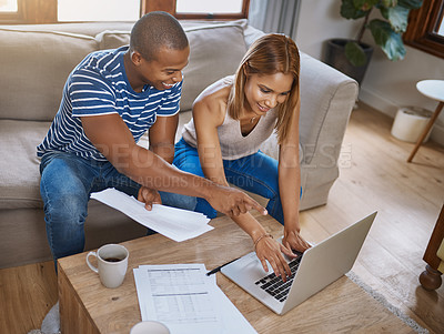 Buy stock photo Shot of a young couple using a laptop while going through their paperwork together at home