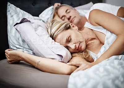 Buy stock photo Cropped shot of a mature couple sleeping in their bed