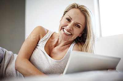 Buy stock photo Shot of a mature woman using her digital tablet while lying in bed