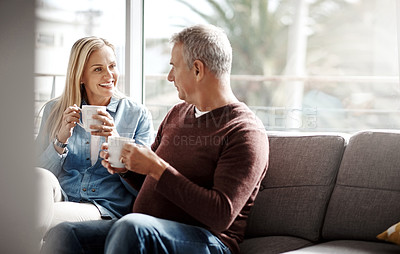 Buy stock photo Shot of a mature couple enjoying a relaxing coffee break on the sofa together at home