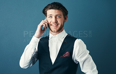 Buy stock photo Studio shot of a handsome young businessman making a phonecall against a blue background