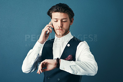 Buy stock photo Studio shot of a handsome young businessman checking the time while making a phonecall against a blue background
