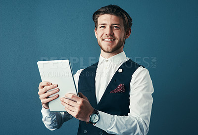 Buy stock photo Studio shot of a handsome young businessman using a tablet against a blue background