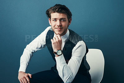 Buy stock photo Studio shot of a handsome young businessman looking thoughtful against a blue background