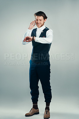 Buy stock photo Studio shot of a handsome young businessman checking the time while making a phonecall against a grey background