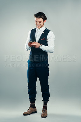 Buy stock photo Studio shot of a handsome young businessman sending a text message against a grey background