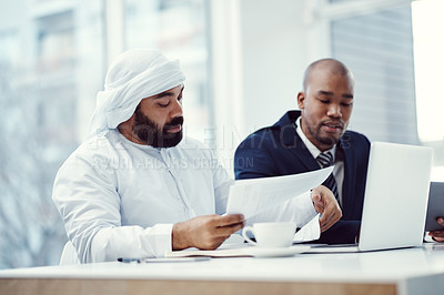 Buy stock photo Shot of two businessmen using a laptop while having a discussion over paperwork in a modern office