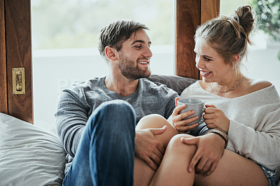 Buy stock photo Shot of a happy young couple enjoying a coffee break together in the bedroom at home