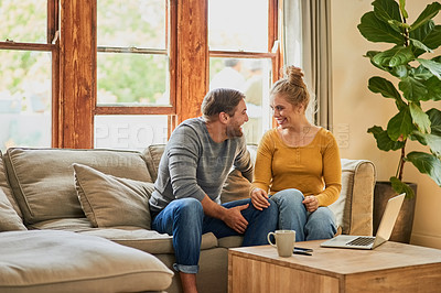 Buy stock photo Shot of a young couple talking on the sofa in the living room at home