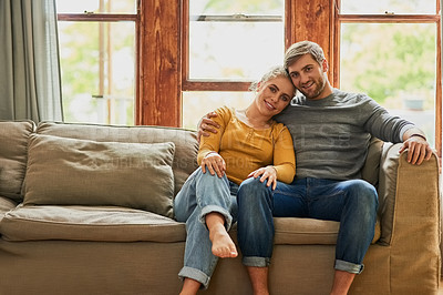 Buy stock photo Portrait of a young couple chilling on the sofa in the living room at home