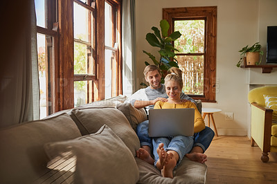 Buy stock photo Shot of a young couple using a laptop together on the sofa in the living room at home