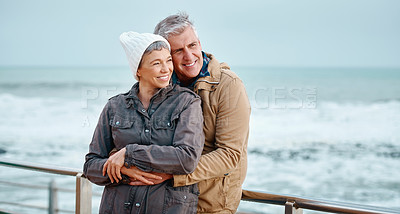 Buy stock photo High angle shot of an affectionate senior couple standing on the promenade at the beach